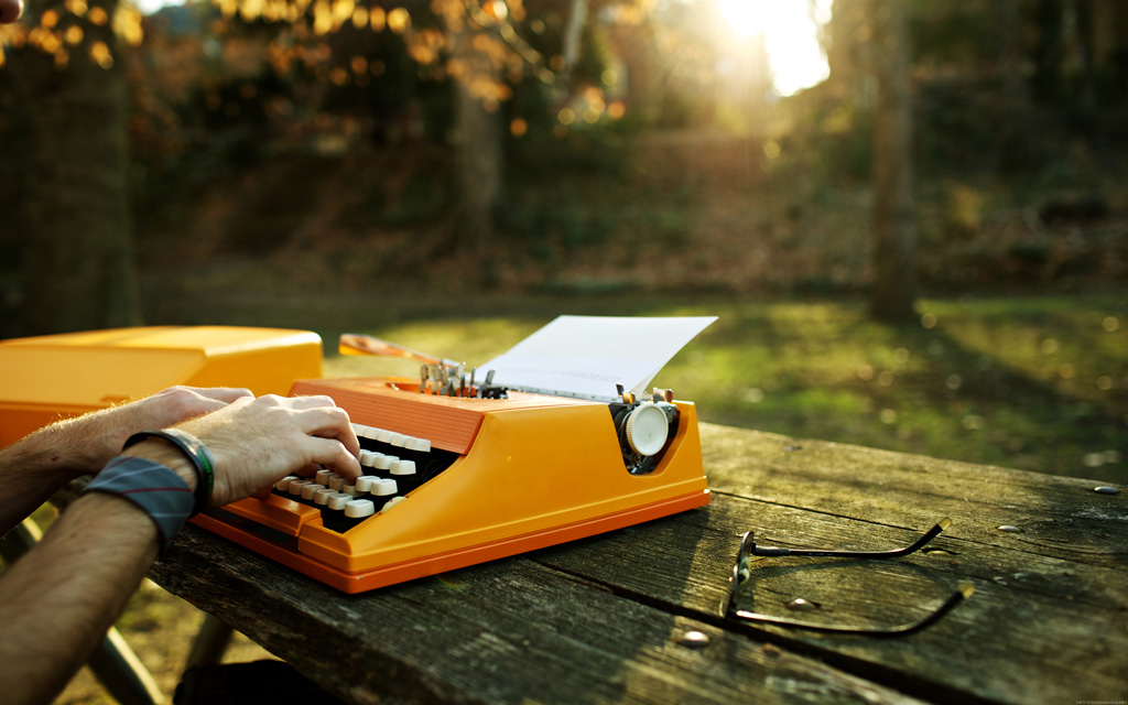 Hands on the orange typewriter in a park